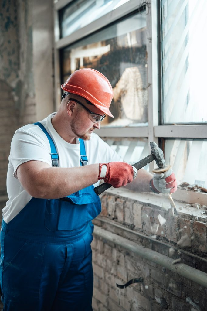 Construction worker working with a hammer, destroying old brick walls